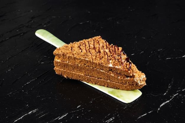Kawałek ciasta miodowego na szpatułce.