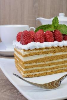 Kawałek ciasta miodowego z bitą śmietaną i malinami