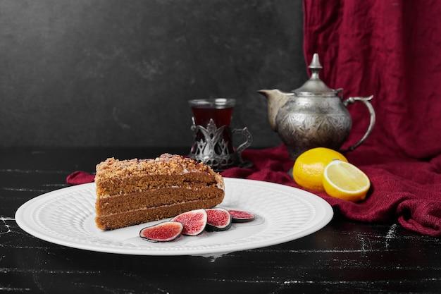 Kawałek ciasta miodowego z figami i herbatą.
