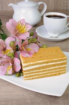 Kawałek ciasta miodowego z filiżanką kawy na stole z kwiatkiem