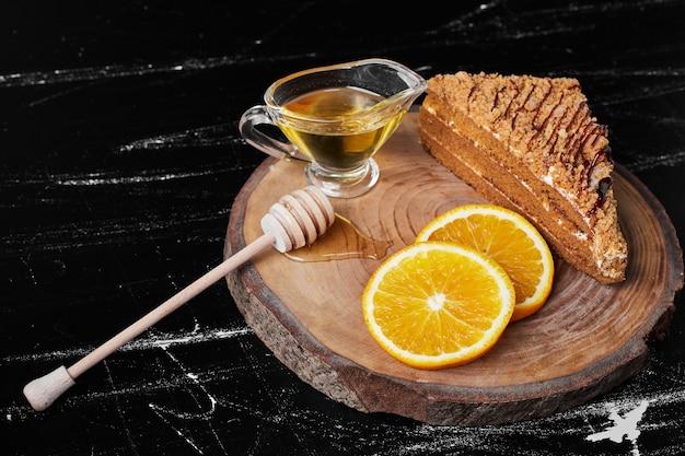 Kawałek ciasta miodowego z plastrami pomarańczy i syropem