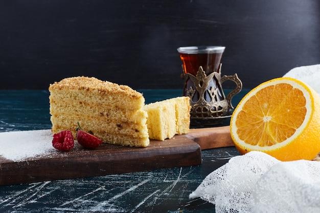 Kawałek ciasta miodowego ze szklanką herbaty.