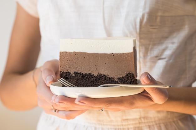 """Kawałek ciasta musowego """"trzy czekoladowe"""" w ręce dziewczynki, posypane czekoladą i ozdobione cukierkami"""