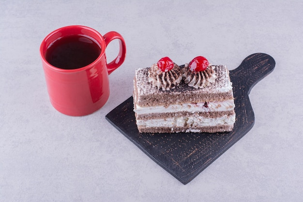 Kawałek ciasta na ciemnym pokładzie z filiżanką herbaty. zdjęcie wysokiej jakości