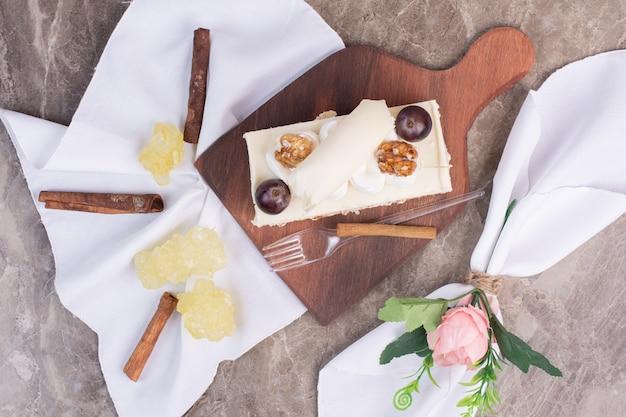 Kawałek ciasta na drewnianej desce z obrusem i cukierkami.
