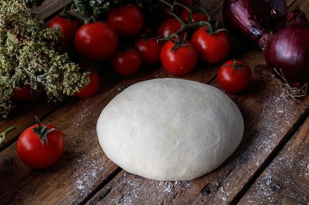 Kawałek ciasta na drewnianym stole w otoczeniu pomidorów i cebuli