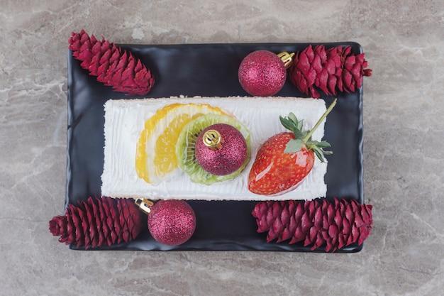 Kawałek ciasta na talerzu ozdobionym świątecznymi dekoracjami na marmurze