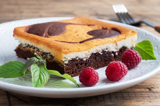 Kawałek ciasta na talerzu z czekoladowymi ciasteczkami i twarogiem z malinami