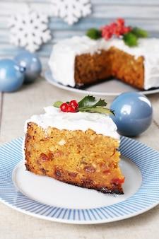 Kawałek ciasta na talerzu z dekoracją świąteczną na drewnianym tle