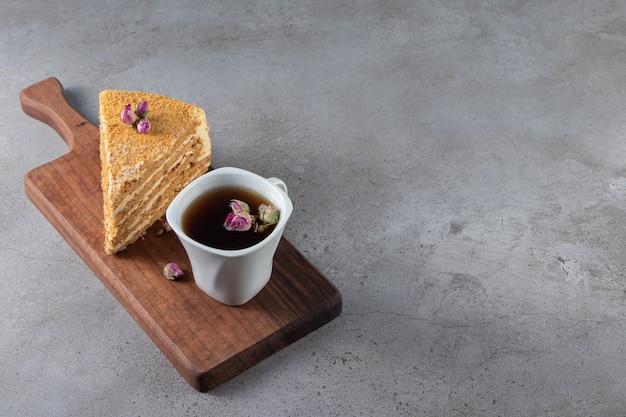 Kawałek ciasta napoleon obok filiżanki herbaty na desce do krojenia, na marmurowym stole.