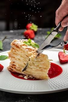 Kawałek ciasta napoleońskiego. napoleon z kremową wanilią z kremem, jabłkami i konfiturą truskawkową ozdobiony miętą, czarne tło dla menu.