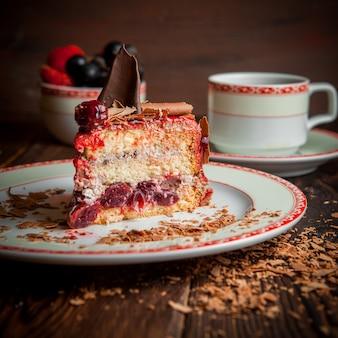 Kawałek ciasta owocowego z kawałkami czekolady i filiżanką herbaty i jagód w okrągłym talerzu