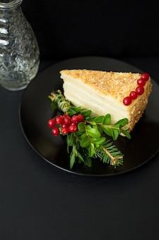 Kawałek ciasta ozdobiony gałęziami i jagodami