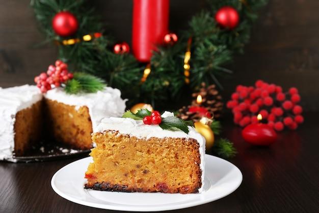 Kawałek ciasta pokryty kremem z dekoracją świąteczną na powierzchni drewnianego stołu