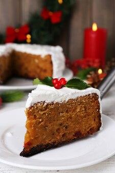 Kawałek ciasta pokryty kremem ze świąteczną dekoracją na stole