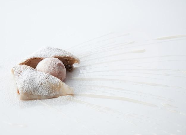Kawałek ciasta polany słodkim sosem na białym tle