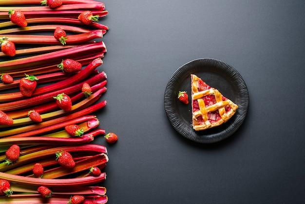 Kawałek ciasta rabarbarowo-truskawkowego na czarnym talerzu
