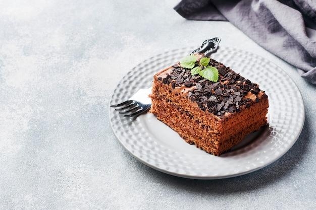 Kawałek ciasta truflowego z czekoladą na szarym tle betonu. skopiuj miejsce