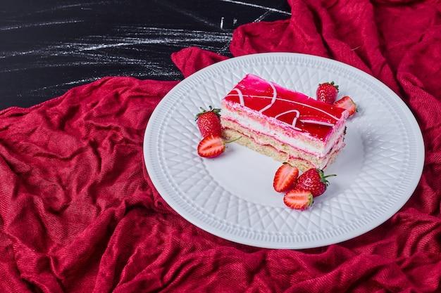 Kawałek ciasta truskawkowego na białym talerzu na ciemnym tle.