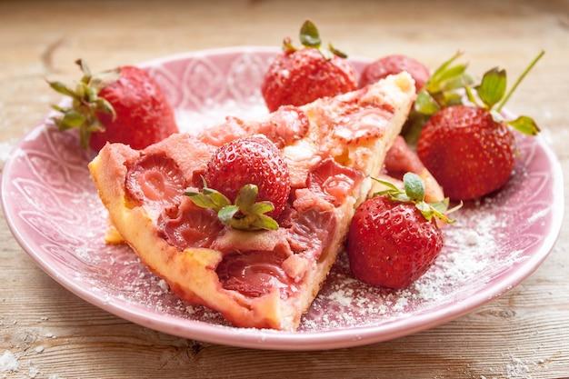 Kawałek ciasta truskawkowego na różowym talerzu z truskawkami