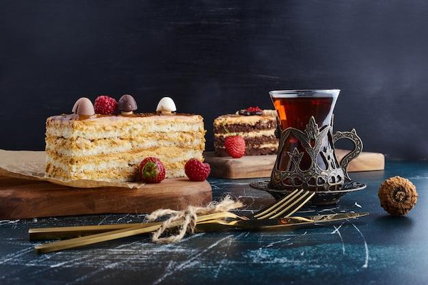 Kawałek ciasta waniliowego ganache ze szklanką herbaty.