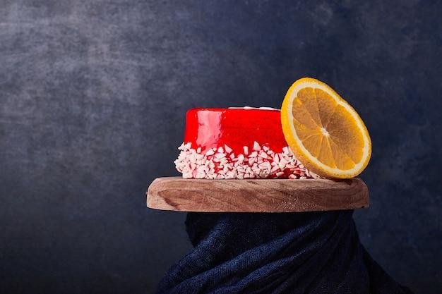 Kawałek ciasta z czerwonym syropem i owocami.