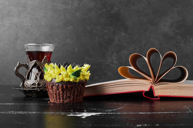 Kawałek ciasta z dekoracją kremu słonecznikowego podawany ze szklanką herbaty.