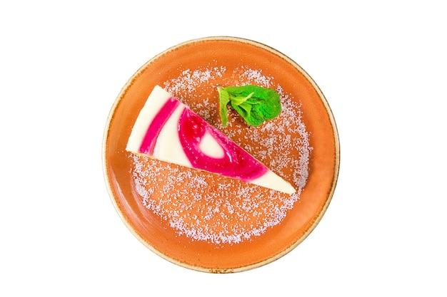 Kawałek ciasta z dżemem jagodowym i kremowym herbatnikiem sufletowym z liśćmi mięty i posypanym cukrem na brązowym talerzu, na białym tle.