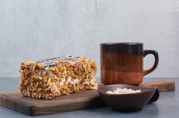Kawałek ciasta z filiżanką aromatycznej kawy na szarym stole.