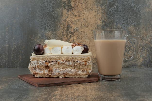 Kawałek ciasta z filiżanką gorącej kawy na marmurowej ścianie