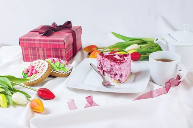 Kawałek ciasta z filiżanką kawy i tulipany