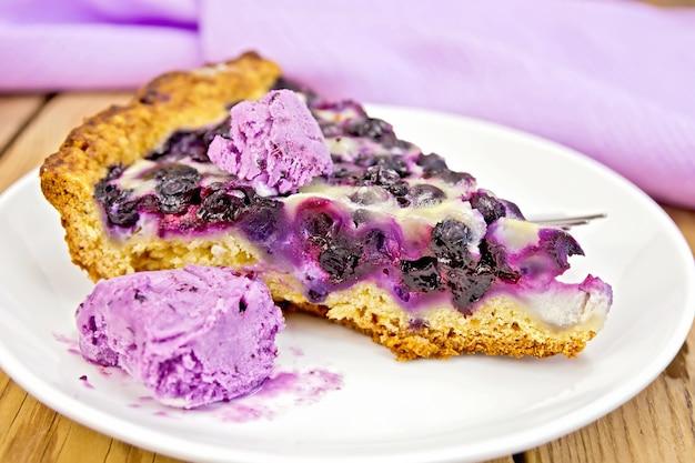 Kawałek ciasta z jagodami, lodami i łyżką oraz w talerzu, serwetka na tle drewnianych desek