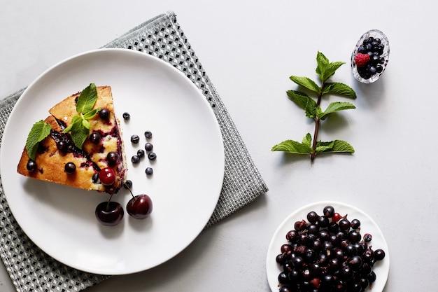 Kawałek ciasta z jagodami, malinami, wiśniami i miętą na deser na białym talerzu, serwetka. kawałki pysznego domowego ciasta