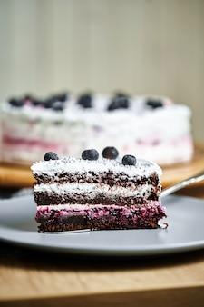 Kawałek ciasta z jagodami na talerzu.