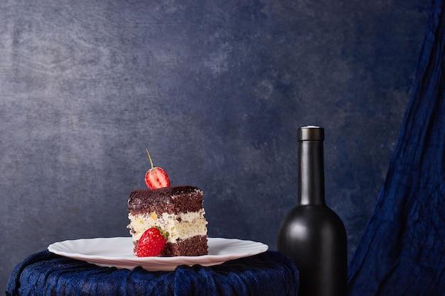 Kawałek ciasta z kakao i truskawkami na białym talerzu.