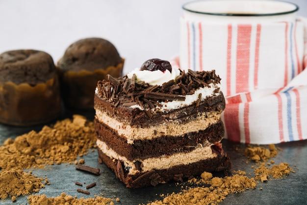 Kawałek ciasta z kakao w proszku i kubek kawy