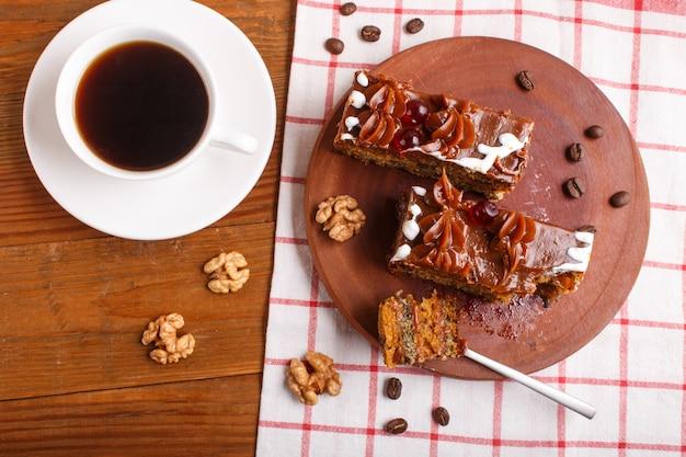 Kawałek ciasta z kremem karmelowym na drewnianej desce kuchennej i filiżankę kawy, brązowe drewniane tła.