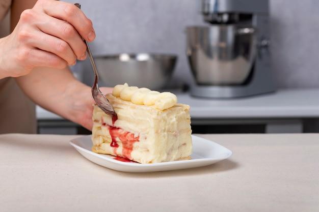 Kawałek ciasta z kremem waniliowo-jagodowym. ręka z łyżką deserową w pobliżu ciasta.