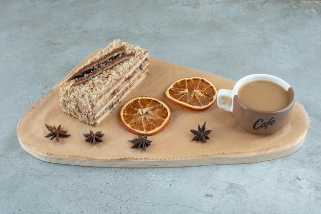 Kawałek ciasta z plastrami pomarańczy i kawy na desce. zdjęcie wysokiej jakości