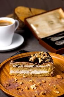 Kawałek ciasta z polewą czekoladową i orzechami podawany z filiżanką kawy
