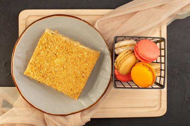 Kawałek ciasta z widokiem z góry na pyszne francuskie macarons i pieczone wewnątrz talerza