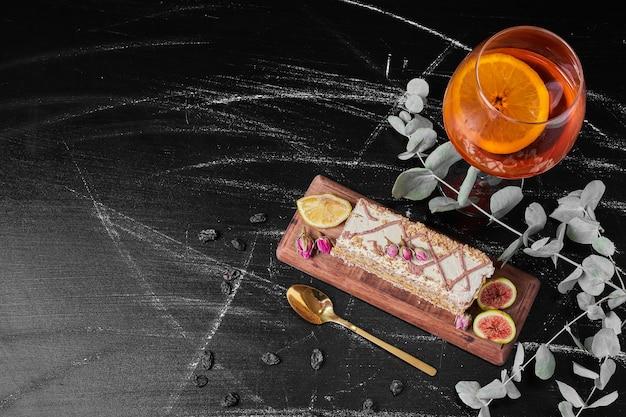 Kawałek ciasta z winem na drewnianym talerzu.