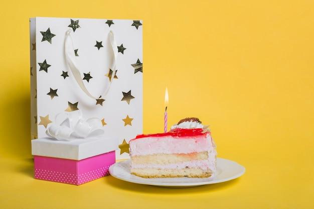 Kawałek ciasta z zapaloną świecą; torba na zakupy w kształcie gwiazdy; i pudełko na żółtym tle