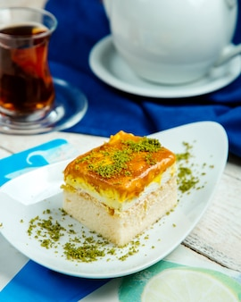 Kawałek ciasta ze śmietaną zwieńczoną syropem karmelowym i pistacją