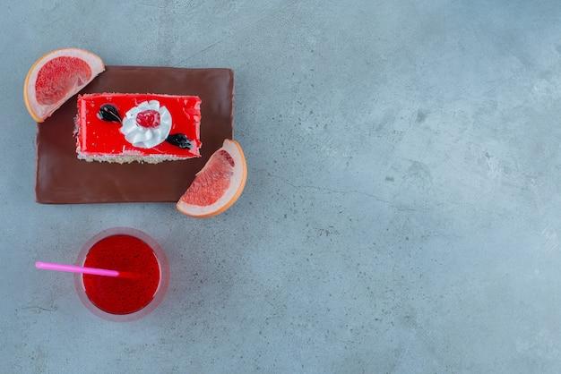 Kawałek ciasta ze szklaną filiżanką czerwonego soku.