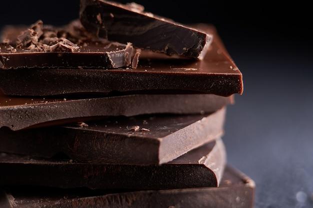Kawałek ciemnej czekolady i wiórków czekoladowych z bliska
