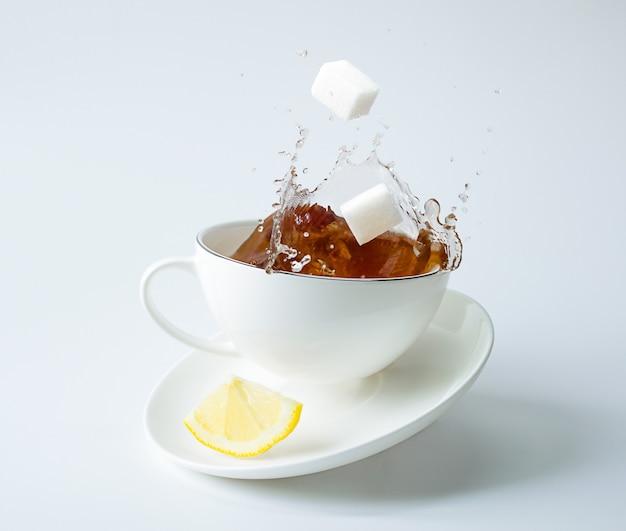 Kawałek cytryny na spodeczku i kostki cukru spadające do filiżanki z plamami. zamarznięte plamy, lewitacja i równowaga.