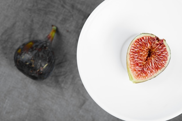 Kawałek czarnej figi na białym talerzu obok całej fig. wysokiej jakości zdjęcie