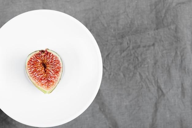 Kawałek czarnej figi na białym talerzu. wysokiej jakości zdjęcie
