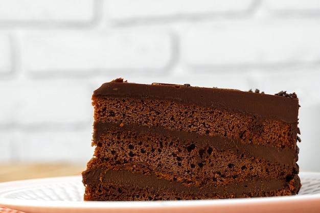 Kawałek czekoladowy tort na bielu talerzu na stole